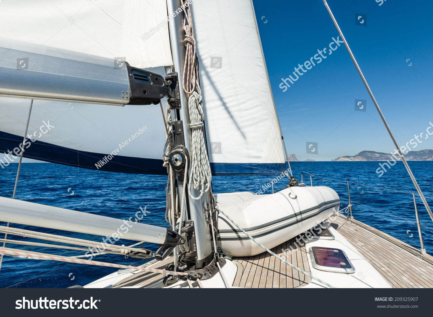 stock-photo-sailing-yacht-going-on-her-sails-in-calm-weather-with-dinghy-on-board-209325907